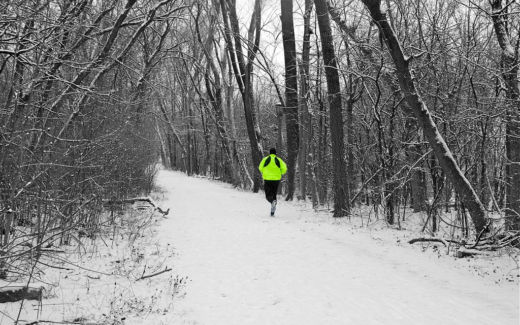 A lonesome runner on a snowy forest-trail.