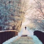 Brücke im Wald mit schneebedeckenten Bäumen, im Sonnenuntergang des Horizonts ein Mann.